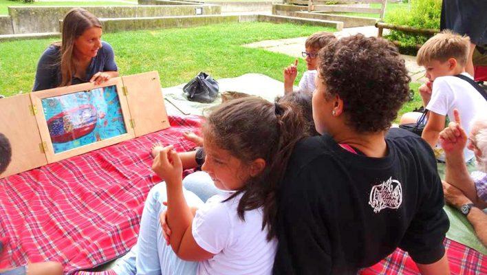 Enfants écoutant une histoire assis sur une pelouse à Bâle