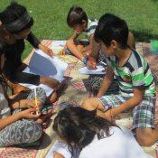Des enfants assis sur une natte dans une pelouse lisent